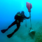 photo of diver with discovery at Butrint V site